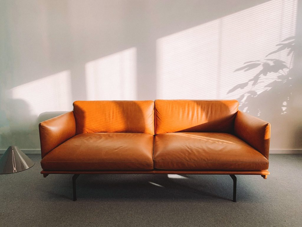 brown leather sofa with light shining in from a window